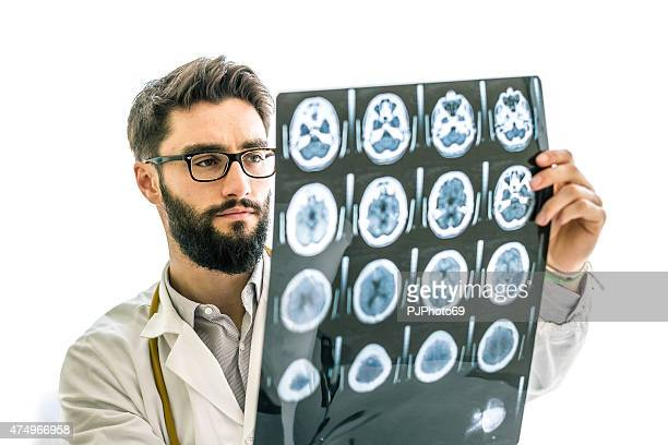 hipster doctor examining the x-ray of brain - male genital organs stock pictures, royalty-free photos & images