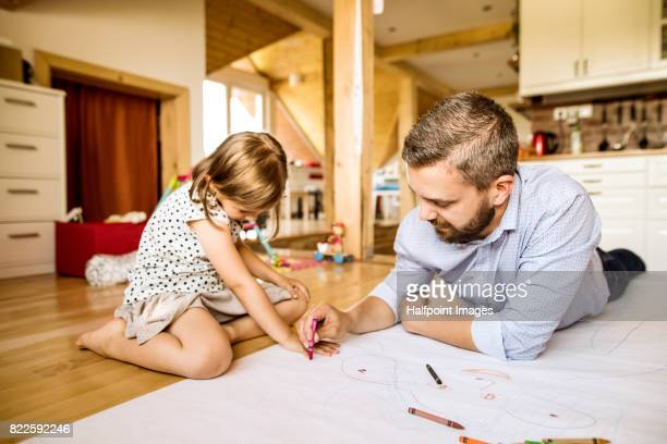 Hipster father and his little daughter drawing together.