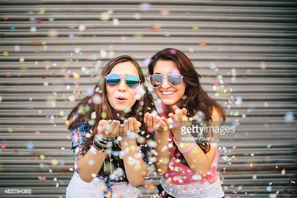 Hipster friends blowing colorful confetti from hands