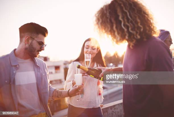 Hipster friends celebrating with champagne at rooftop summer party