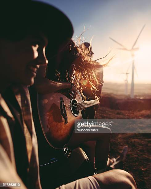 Hipster friends enjoying road trip with a guitar during sunset