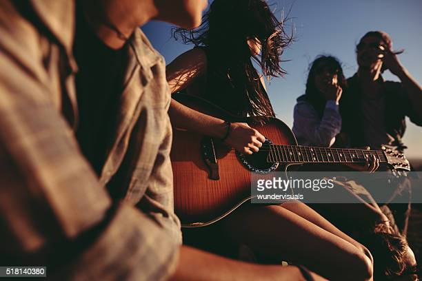 Hipster Friends having fun singing together with a guitar outdoors