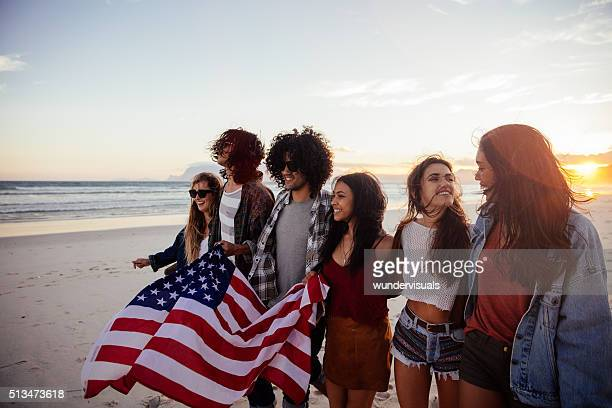 Hipster friends holding an American flag during a beach walk