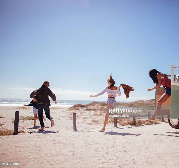 Hipster friends jumping out of Road Trip van at beach