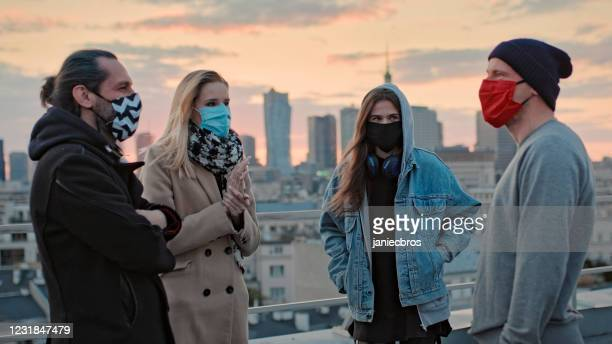 hipster friends meeting on a rooftop. social life during pandemic - small group of people stock pictures, royalty-free photos & images