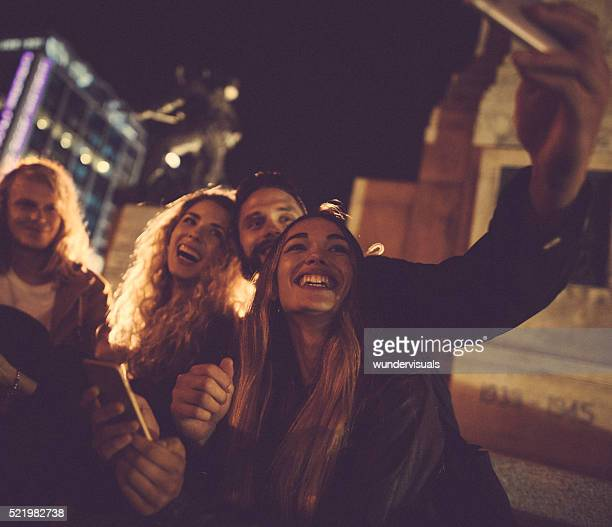 Hipster friends taking a night selfie in town