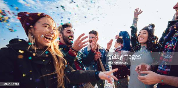 Hipster friends throwing confetti and celebrating together