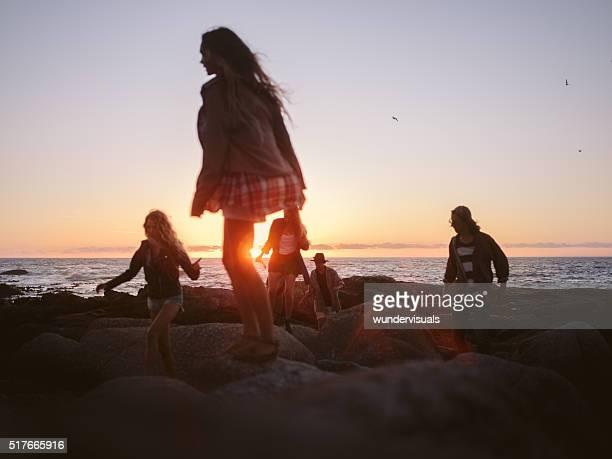 Hipster friends walking on rocks at beach on summertime sunset