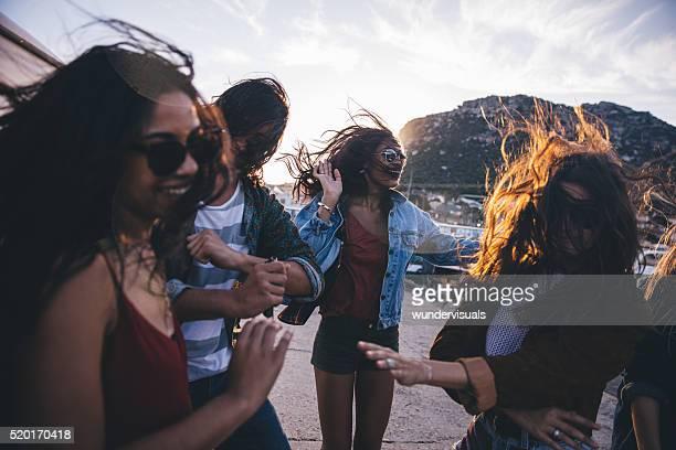 Hipster unterhaltsame Freunde tanzen im Hafen bei Sonnenuntergang