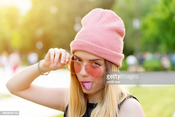 Hipster Girl in pink Beanie Hat in park