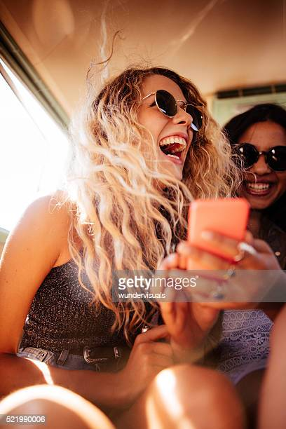 hipster girl looking at smart phone with road trip friend - vertical stock pictures, royalty-free photos & images