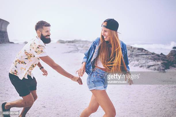 Hipster girl making her boyfriend chase her on the beach
