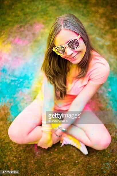 Hipster Mädchen Sitzen im Holi Festival mit bunten Pulver