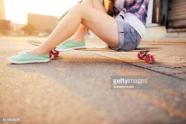 Hipster Menina sentada longboard durante o pôr do sol na Cidade
