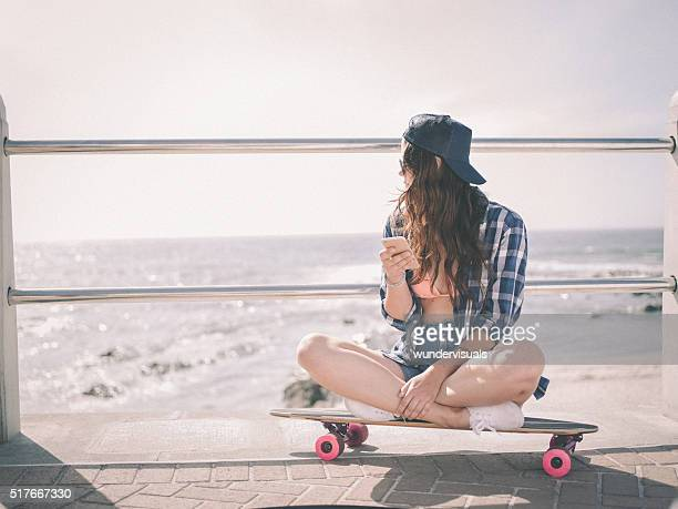 Hipster girl sitting on her skateboard at the beachfront