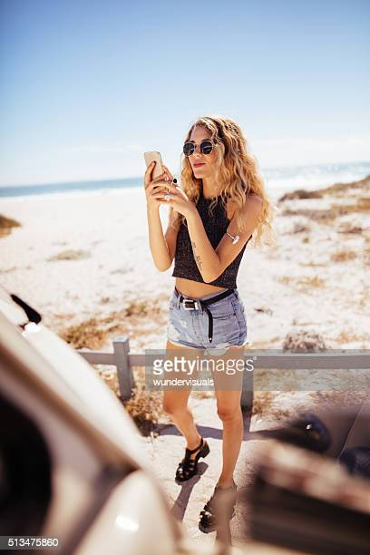 hipster girl taking photo of road trip van with phone - bottomless girl stock pictures, royalty-free photos & images