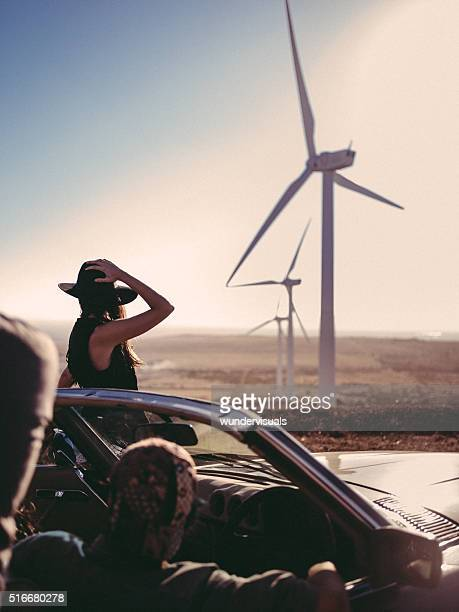 Hipster girl watching wind turbine from car on road trip