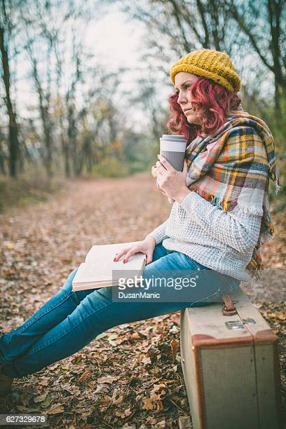hipster girl with coffee cup and book, sitting on suitcase