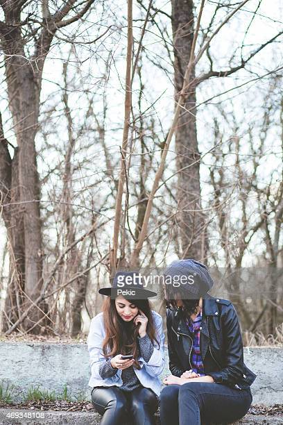 Hipster girls having fun with smart phone in nature