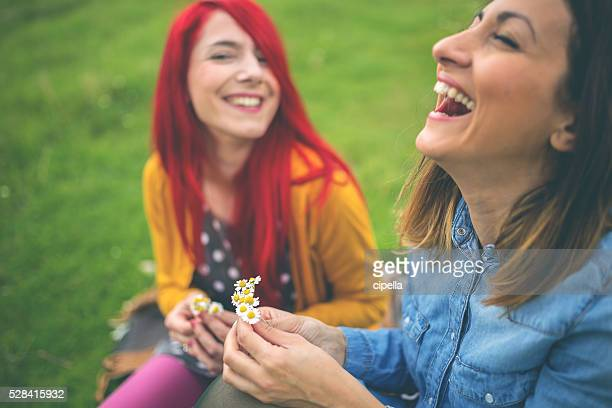 Hipster girls laughing and picking flowers