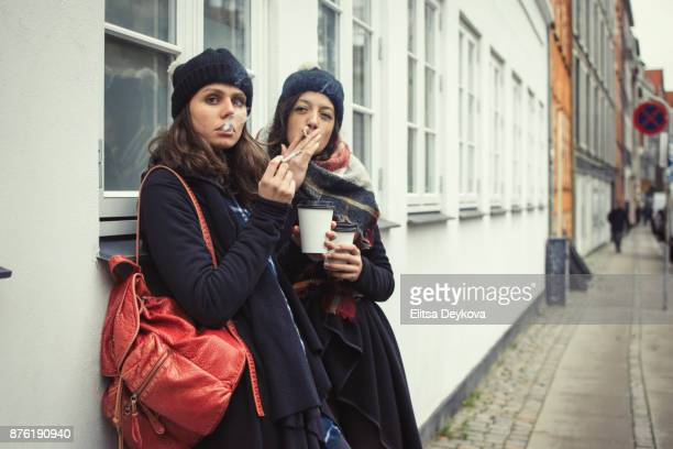 hipster girls smoking a sigarette - smoking issues stock pictures, royalty-free photos & images