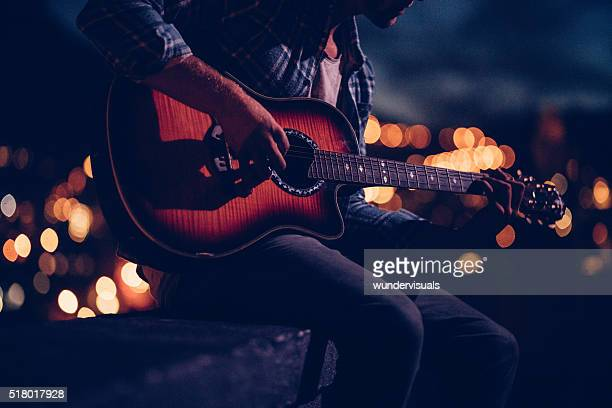 hipster guitarist playing on a rooftop at night - acoustic guitar stock pictures, royalty-free photos & images