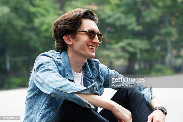 Hipster guy laughing in park