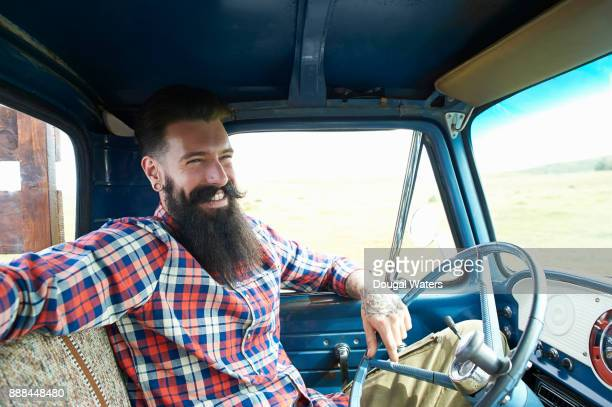 Hipster guy on road trip and laughing.