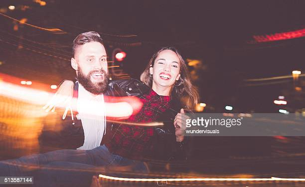 Hipster guy picks his girlfriend up at night in city