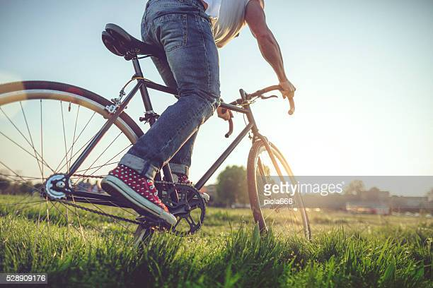 Hipster  guy riding his bicycle on the grass