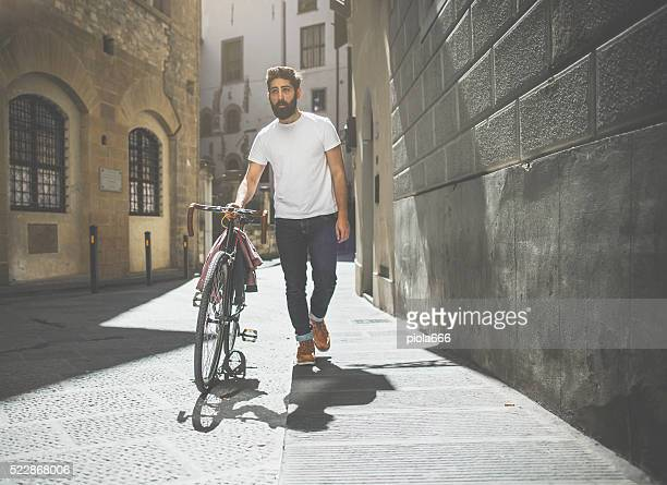 Hipster  guy walking with bicycle
