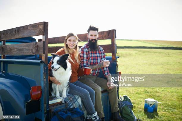 Hipster hiking couple and dog on road trip.