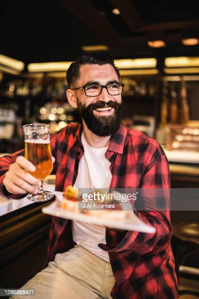 hipster in bar drinking alcohol. beer and tapas - southern european descent stock pictures, royalty-free photos & images
