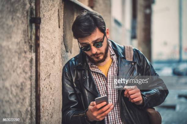 hipster in leather jacket texting - biker jacket stock photos and pictures