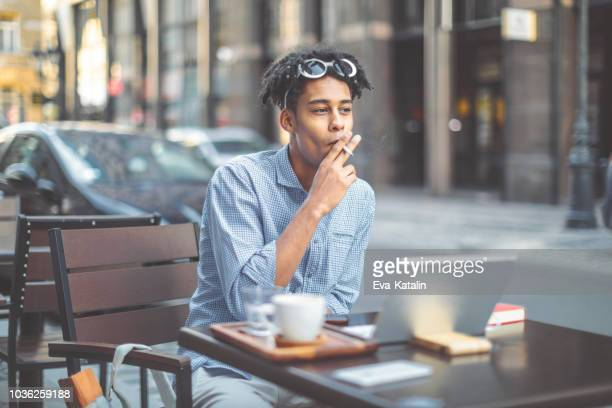 hipster is smoking a cigarette in a sidewalk cafe - cigarette stock pictures, royalty-free photos & images