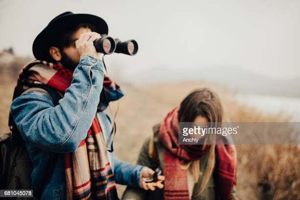 Hipster looking through binoculars and holds compass in the other hand.