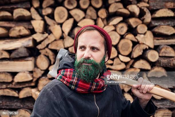 Hipster bûcheron vert scintillant homme avec barbe avec bûches.