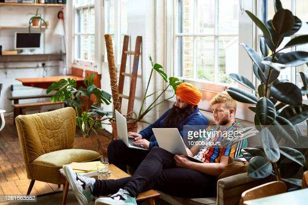 hipster male colleagues working on sofa - headwear stock pictures, royalty-free photos & images