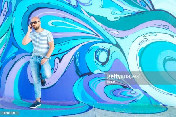hipster male next to wall of graffiti in belgrade - murale foto e immagini stock