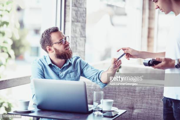 Hipster Male Paying By Credit Card In The Coffee Bar