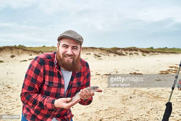 Hipster male proudly holding a fish he caught