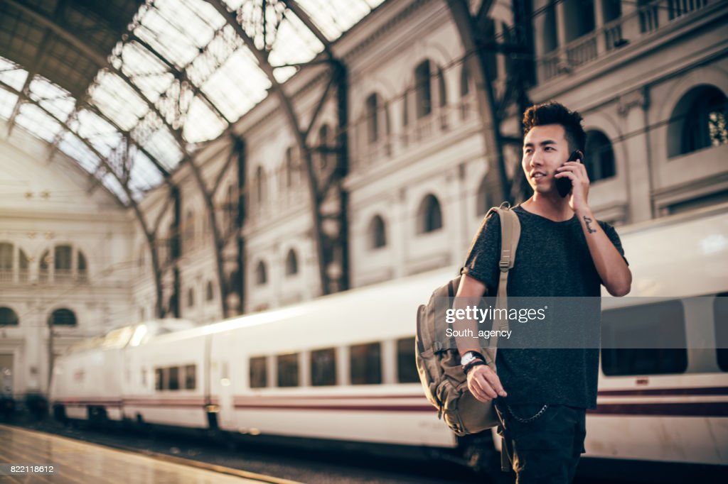 Hipster Man at train station using phone : Stock Photo