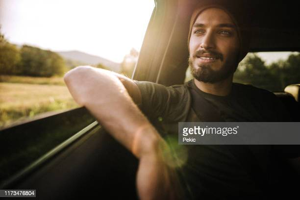 hipster man enjoying the ride on the back seat in car - one man only stock pictures, royalty-free photos & images