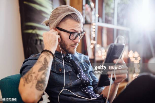 Hipster man fixing his earphone and watching vodcast