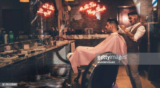 hipster man getting haircut by barber in vintage barber shop - barber shop stock photos and pictures