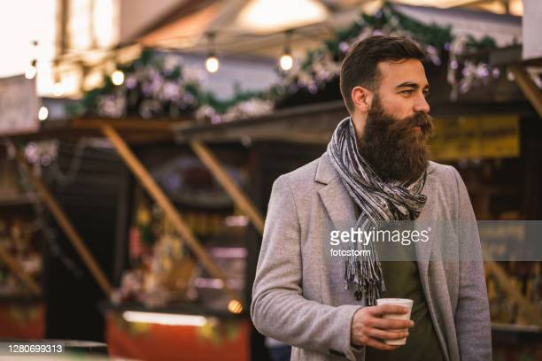 hipster man holding his drink on the street market event - beard stock pictures, royalty-free photos & images