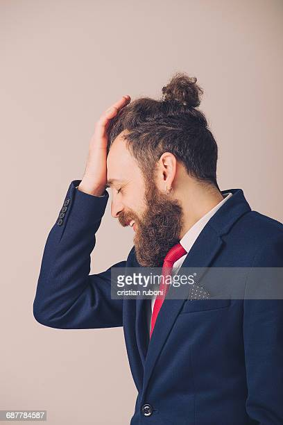 Hipster man in a suit with his hand on his forehead