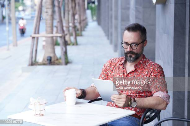 hipster man in cozy sits reading tablet and drink coffee - coffee drink stock pictures, royalty-free photos & images