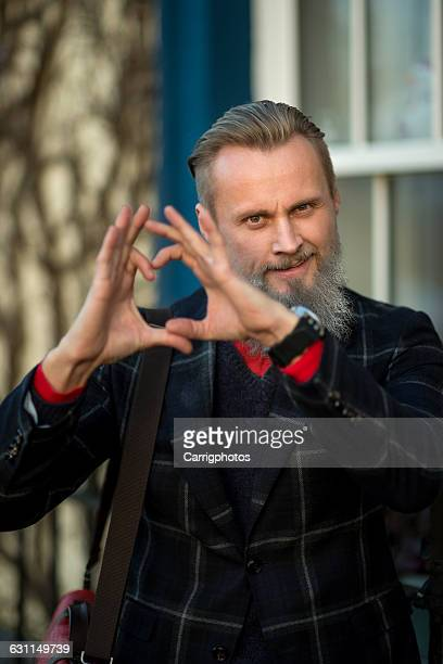 Hipster Man making heart shape with hands