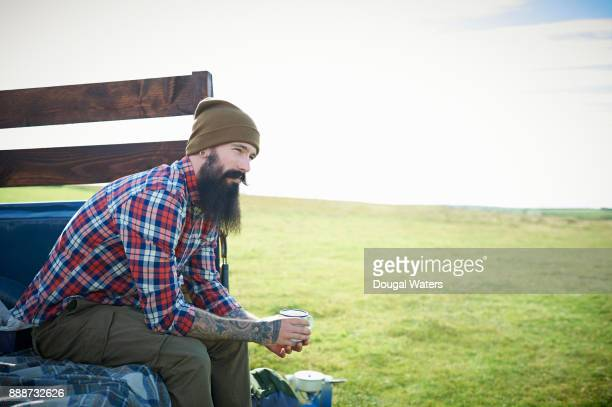 Hipster man on hiking road trip with hot drink.
